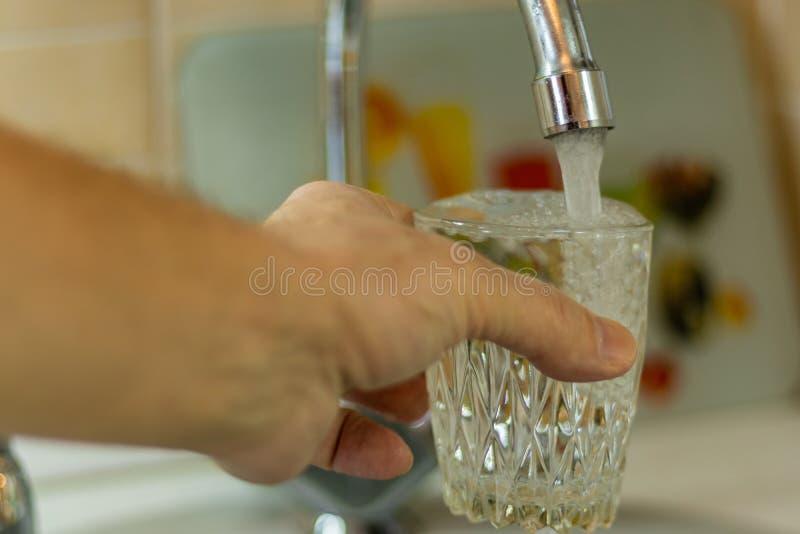 A mão de um homem derrama a água em um vidro sob uma torneira na cozinha imagem de stock royalty free