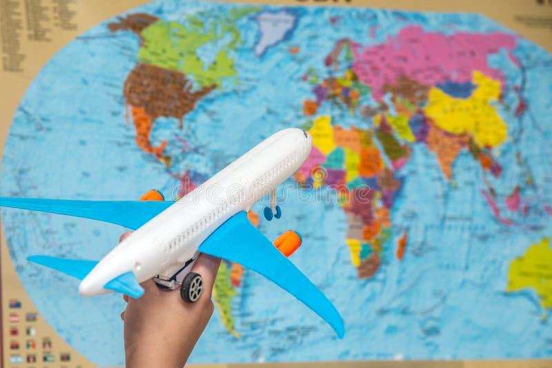 A mão de um homem guarda um plano com as asas azuis na perspectiva do atlas do mundo O conceito do curso em torno do foto de stock royalty free