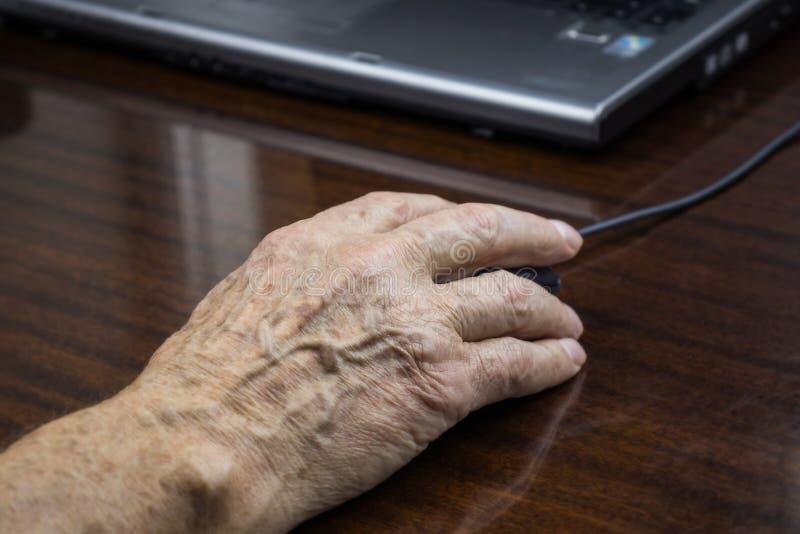 A mão de um homem idoso usa um rato do computador imagens de stock royalty free