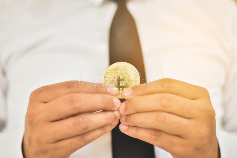 Mão de um homem de negócios que guarda um bitcoin O conceito do dinheiro e fotos de stock royalty free