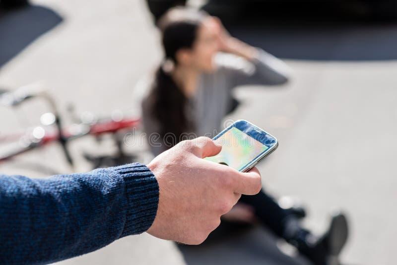 Mão de um homem que chama o número de emergência para uma mulher ferida imagens de stock royalty free