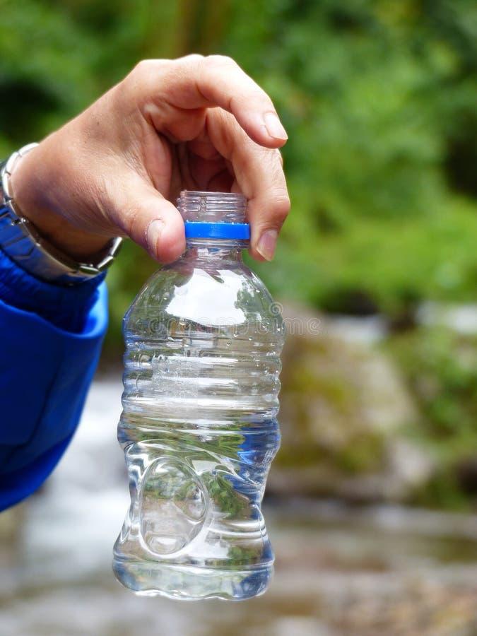 Mão de um homem que mostra uma garrafa plástica com a amostra de água fresca de um córrego foto de stock royalty free