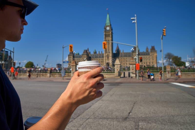 A mão de um jovem está segurando uma xícara de café descartável ou outra bebida quente Rua desfocada e parlamento em Otava fotos de stock royalty free