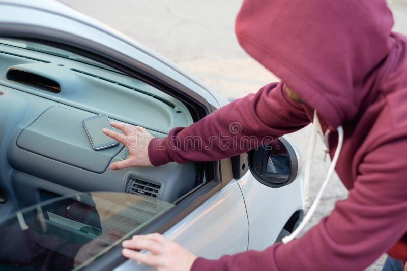 Mão de um ladrão que rouba um telefone celular foto de stock