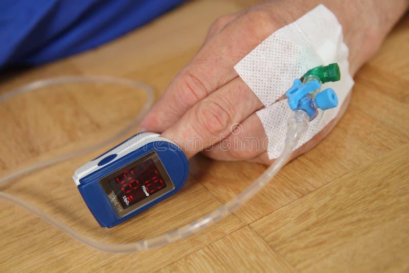 Mão de um paciente com o pulso oximetry fotografia de stock
