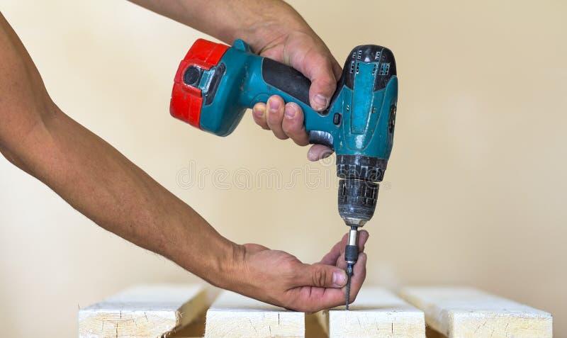 A mão de um trabalhador parafusa um parafuso em uma placa de madeira com cordles foto de stock royalty free