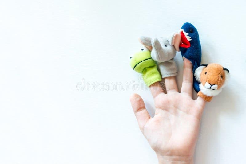 A mão de uma criança com fantoches do dedo, brinquedos, bonecas fecha-se acima no fundo branco com espaço da cópia - jogar o teat imagens de stock