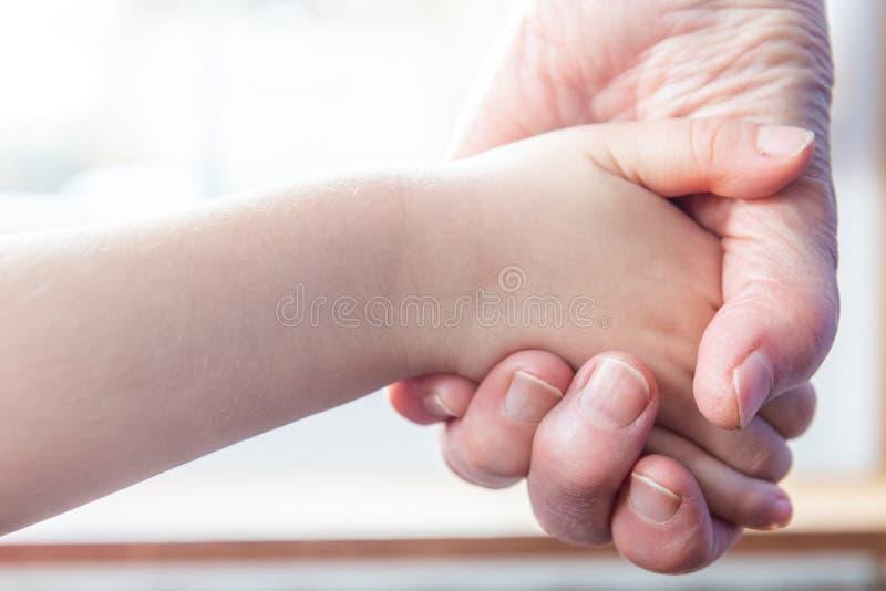 A mão de uma criança na mão de sua avó idosa fotos de stock