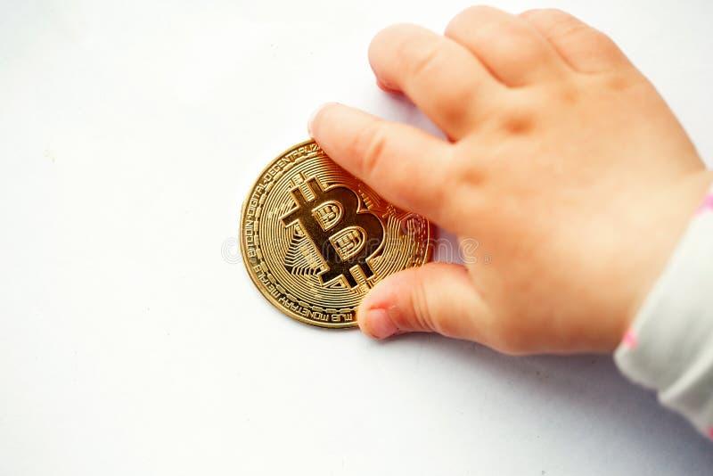 A mão de uma criança pequena alcança para uma moeda do bitcoin fotos de stock royalty free