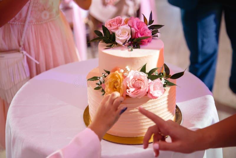 A mão de uma criança que inclina-se para o bolo de casamento no estilo natural ecológico - seu pai mostra com seu dedo que ele imagens de stock royalty free