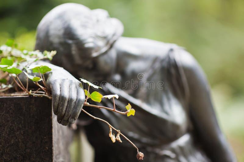 A mão de uma estátua mantem wilted levantou-se fotos de stock