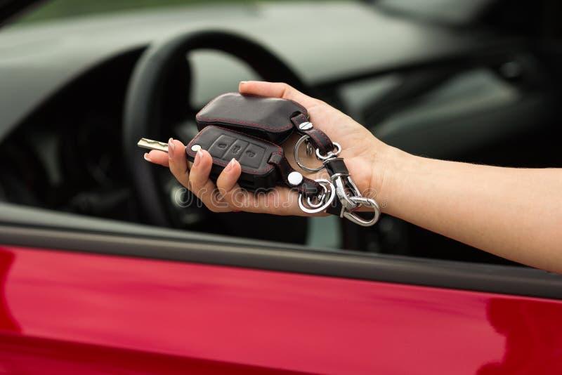Mão de uma menina com uma chave do carro à disposição, em um fundo vermelho do carro fotografia de stock royalty free