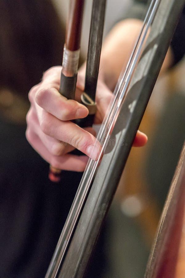 Mão de uma menina que joga um close up do violoncelo contrabass foto de stock