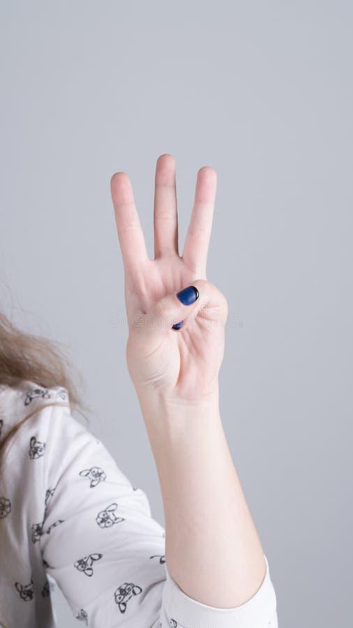 Mão de uma menina que mostra três dedos fotos de stock