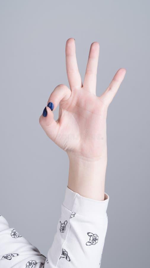 Mão de uma menina que mostra três dedos imagem de stock