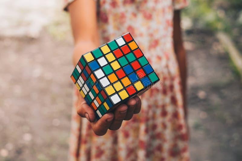 Mão de uma moça que guarda o cubo foto de stock