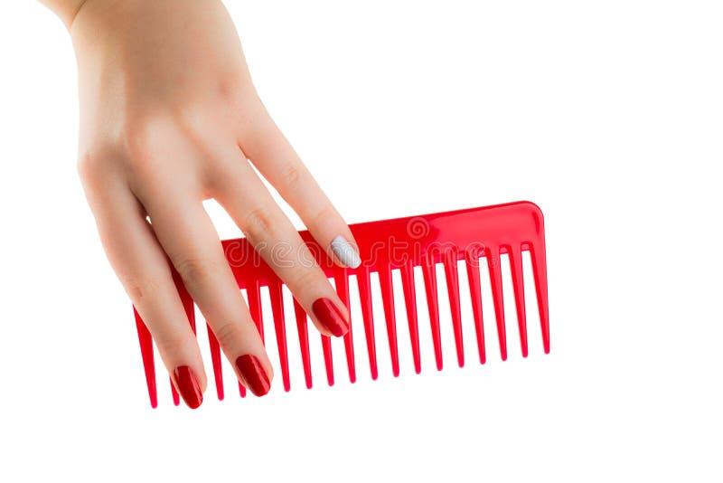 A mão de uma moça toma a escova plástica vermelha imagens de stock royalty free