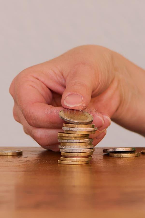 Mão de uma mulher com uma pilha de uma e dois moedas do Euro imagem de stock royalty free