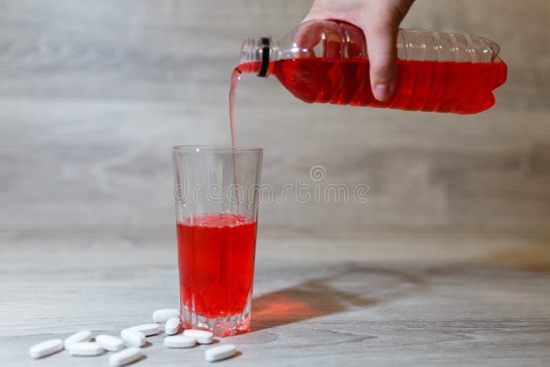 A mão de uma mulher derrama esportes vermelhos bebe ou limonada em um copo de vidro de uma garrafa plástica Bebida da energia no  fotografia de stock
