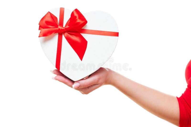 A mão de uma mulher e com vermelho da caixa de presente coração-deu forma, isolado no fundo branco Tema do dia de Valentim fotos de stock