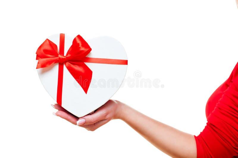 A mão de uma mulher e com vermelho da caixa de presente coração-deu forma, isolado no fundo branco Tema do dia de Valentim foto de stock royalty free