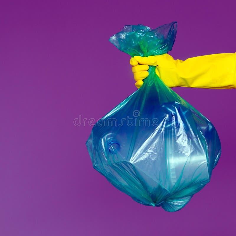 A mão de uma mulher em uma luva de borracha guarda um saco de lixo verde transparente com as garrafas plásticas vazias fotografia de stock