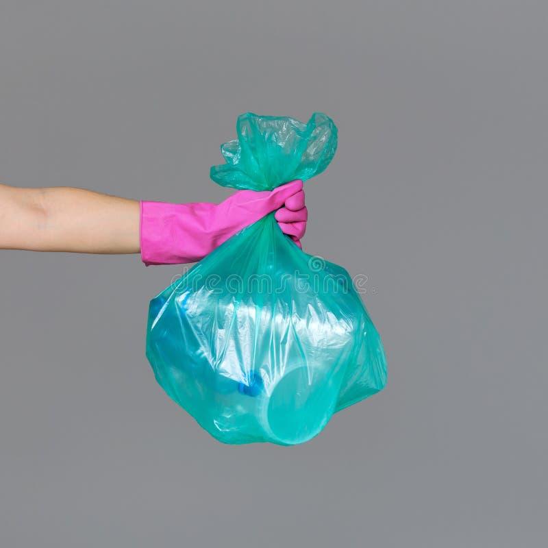 A mão de uma mulher em uma luva de borracha guarda um saco de lixo verde transparente com as garrafas plásticas vazias fotografia de stock royalty free