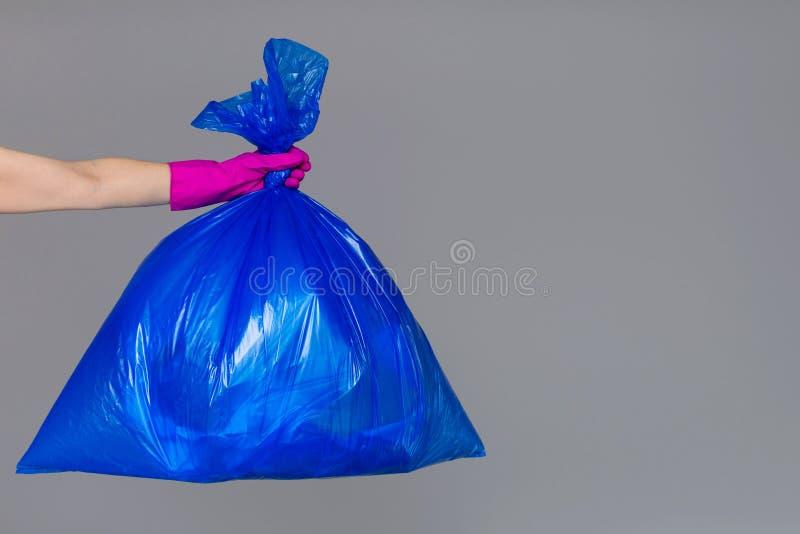 A mão de uma mulher em uma luva de borracha guarda um saco de plástico azul imagem de stock royalty free