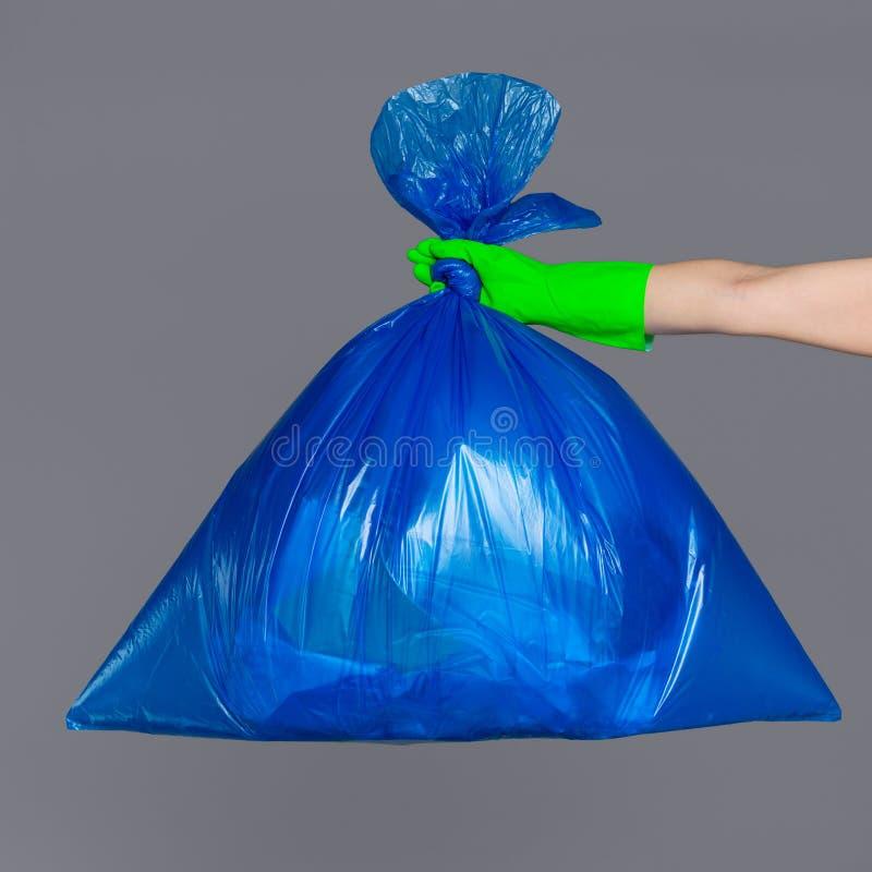 A mão de uma mulher em uma luva de borracha guarda um saco de plástico azul foto de stock