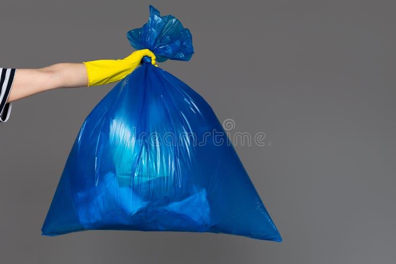 A mão de uma mulher em uma luva de borracha guarda um saco de plástico azul completamente de lixo imagens de stock