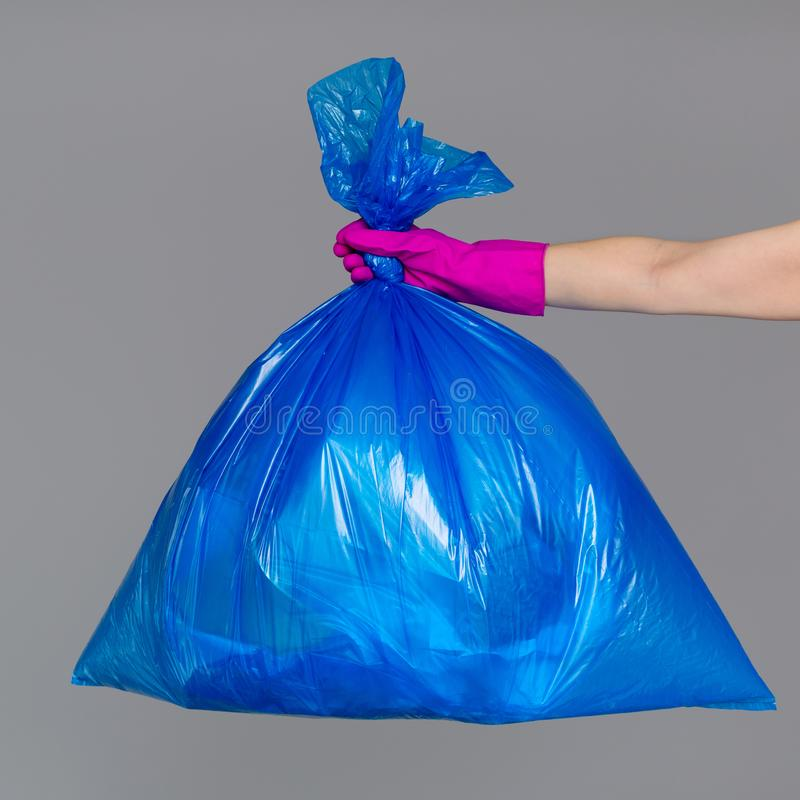 A mão de uma mulher em uma luva de borracha guarda um saco de plástico azul foto de stock royalty free