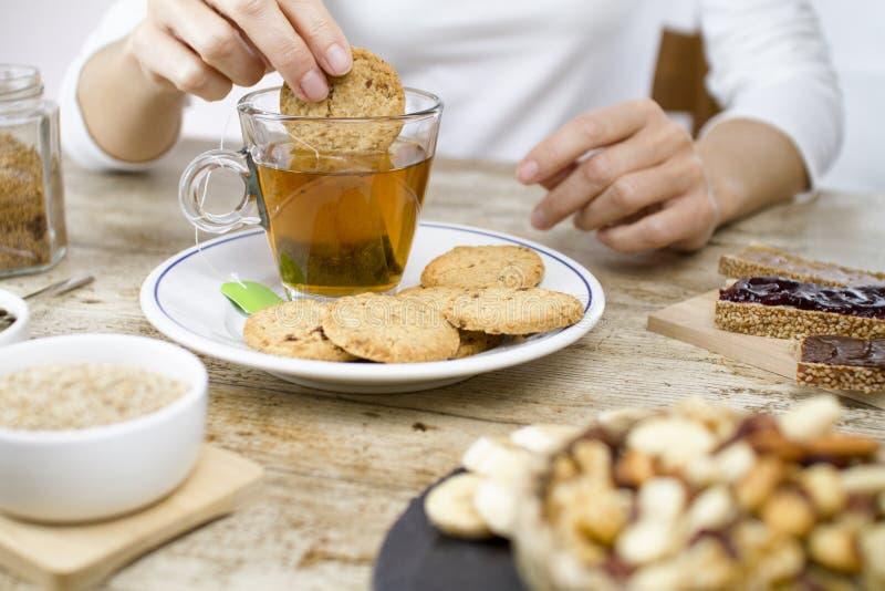 A mão de uma mulher na tabela em uma tabela de madeira ajustada para um café da manhã doce do vegetariano com uma fatia de banana imagem de stock royalty free