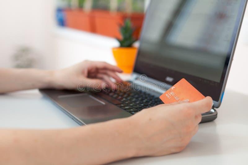 Mão de uma mulher que faz compras através do Internet Compra em linha Focalize na mão e no cartão fotografia de stock