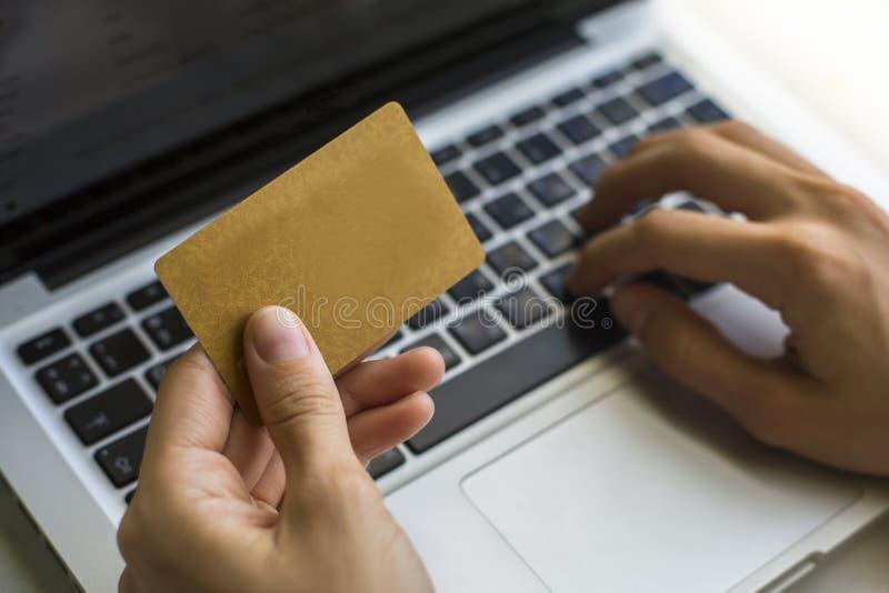 Mão de uma mulher que faz compras através do Internet, do teclado e do cartão imagens de stock