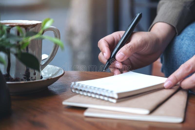 A mão de uma mulher que prepara-se para escrever no caderno vazio fotos de stock royalty free