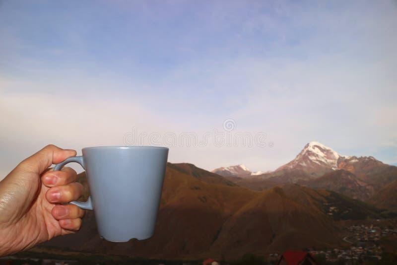 Mão de Vestido Segurando uma Xícara de Café da Manhã com Montanhas Blurry Snow Capped no Fundo fotos de stock
