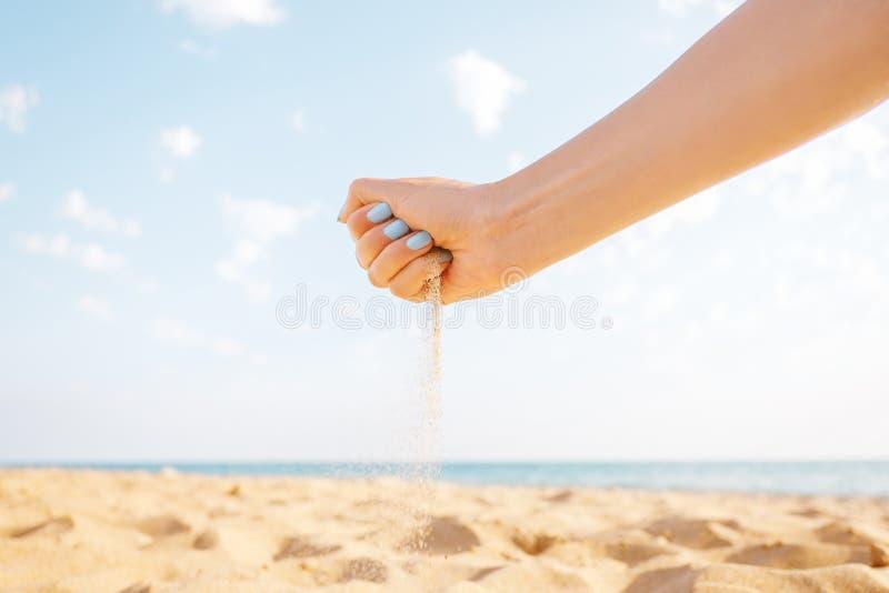 A mão de Woman's derrama a areia exterior imagens de stock