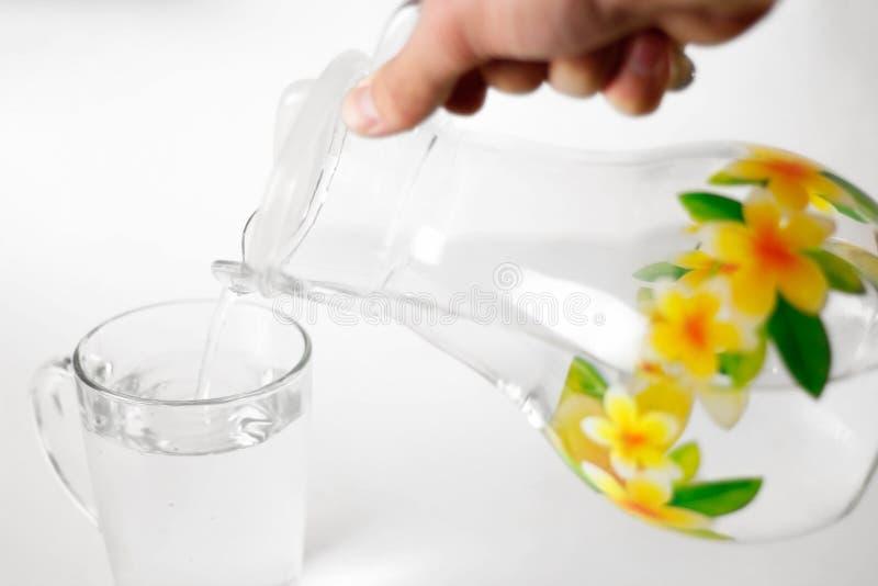 A mão derrama a água em um copo de vidro de vidro de um jarro de vidro Fim acima Isolado no fundo branco fotografia de stock royalty free