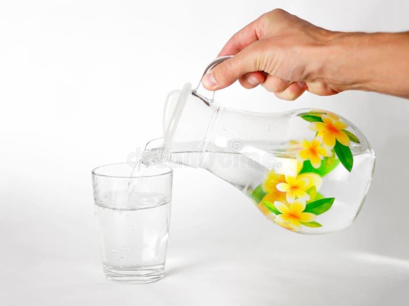 A mão derrama a água em um copo de vidro de vidro de um jarro de vidro Fim acima No fundo branco foto de stock