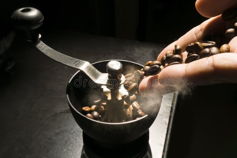 A mão derrama feijões de café no moedor com fumo, no conceito do fabricante da bebida do café fotos de stock