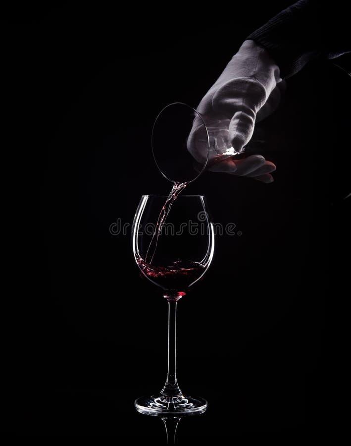 A mão derrama o vinho tinto do filtro ao vidro imagem de stock