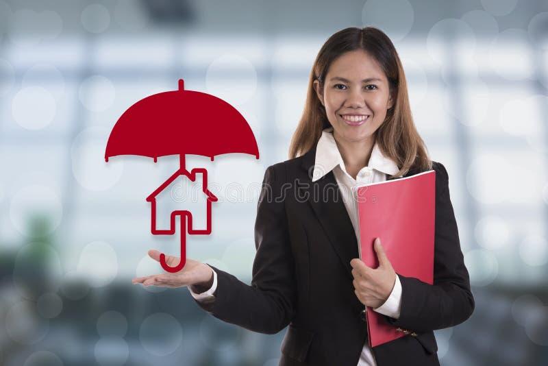 Mão do agente do vendedor que mantém a proteção do guarda-chuva home fotos de stock