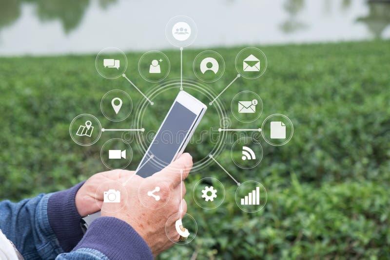 Mão do ancião do close up usando o smartphone e o ícone visual no móbil fotografia de stock