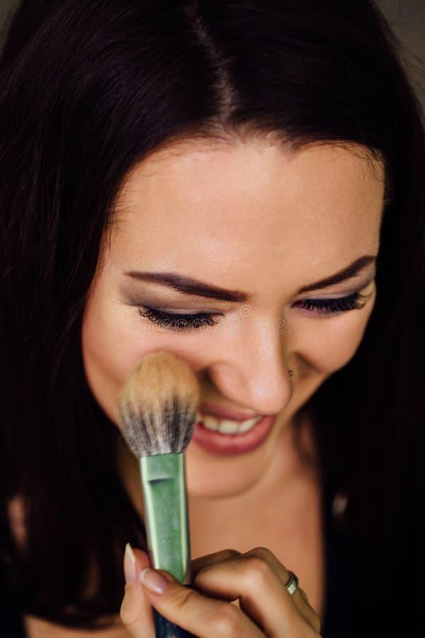 Mão do artista de composição que aplica a cor baixa brilhante na cara modelo do ` s e que guarda uma escova, fim fotografia de stock