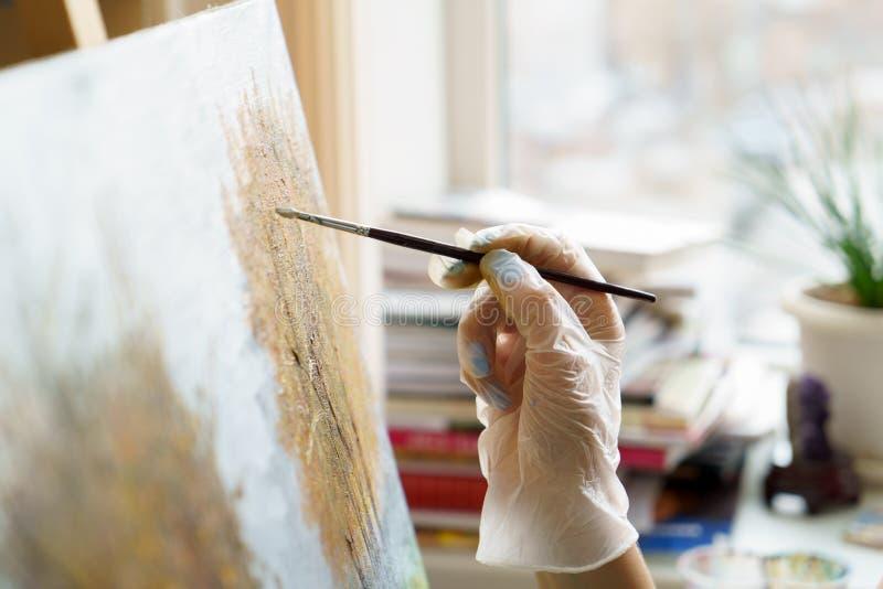 A mão do artista tira a pintura a óleo perto acima imagens de stock