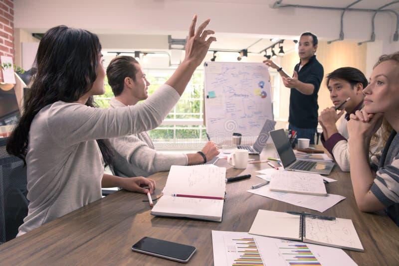 A mão do aumento da mulher de negócio para faz a pergunta ao homem de negócios que é estando e de explicação a carta na frente da fotografia de stock royalty free