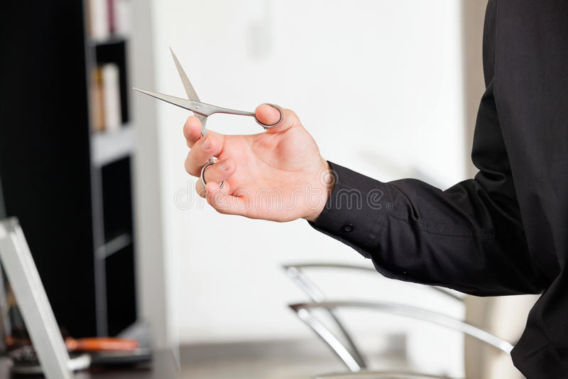 A mão do barbeiro masculino que guarda tesouras foto de stock royalty free