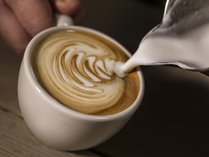 Mão do barista que faz o leite de derramamento do café do cappuccino que faz o lat foto de stock