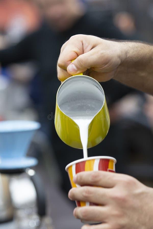 A mão do barman, derrama o milk shake em um vidro imagens de stock royalty free