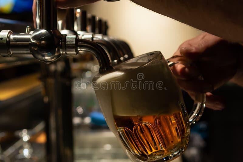 Mão do barman que derrama uma grande cerveja de cerveja pilsen na torneira Resto em uma barra com amigos foto de stock royalty free